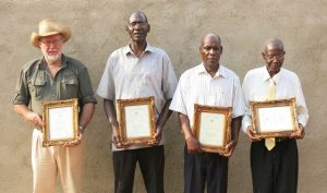"""FOUNDER MEMBERS OF THE MAHENYE CAMPFIRE PROJECT RECEIVING AN AWARD (CLIVE STOCKHIL ON THE LEFT) (From the talk by Clive Stockil """"History of the First Campfire Project in Zimbabwe"""")"""